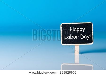 Labour Day - May 1st. Day 1 Of Month, Text At Little Woden Tag On Blue Background With Copy Space. S