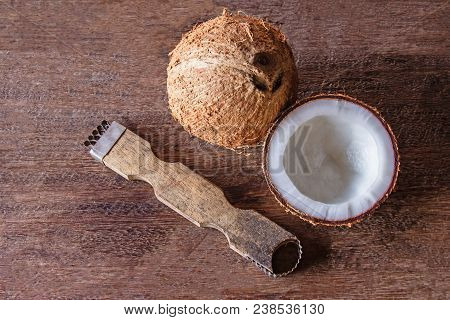 The tool for scraping the coconut meat small on wood floor. Top view poster