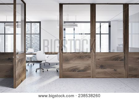 White Boardroom Interior With A Concrete Floor, A Long Wooden Table And White Chairs. Wooden Wall Lo