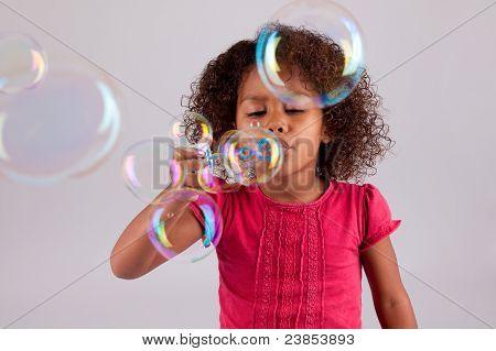 Africana menina asiática soprando bolhas de sabão
