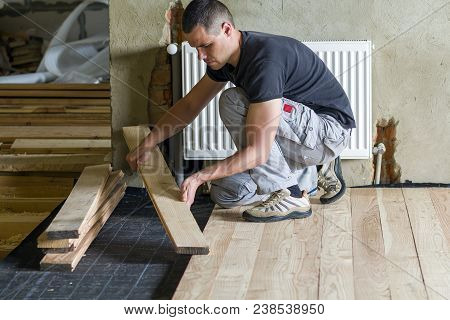 Young Handsome Professional Carpenter Installing Natural Wooden Planks On Wooden Frame Floor In Empt