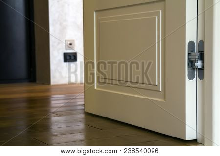 Modern House Interior Detail With Wooden Parquet Floor And White Door. Apartment After Renovation Cl