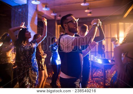 Crowd Of Trendy  People Dancing In Nightclub With Golden Confetti Flying Around, Focus On Asian Man