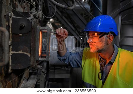 Industrial worker checking recycling oven