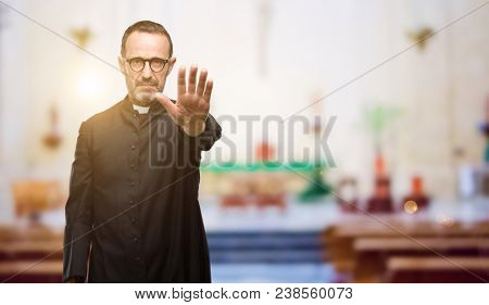 Priest religion man annoyed with bad attitude making stop sign with hand, saying no, expressing security, defense or restriction, maybe pushing at church
