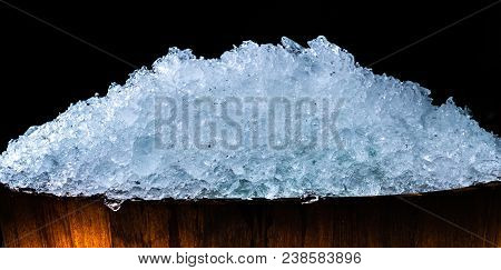 Pile Of Crushed Ice Cubes In Wood Bucket On Dark Background With Copy Space. Crushed Ice Cubes Foreg
