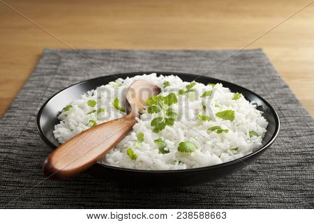 Basmati Rice With Coriander And A Wooden Spoon In A Black Bowl, On A Grey Mat, On A Wooden Table. Tr