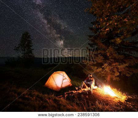 Romantic Couple Hikers Sitting On Log Beside Illuminated Orange Tent, Hugging And Admire Scenery Of