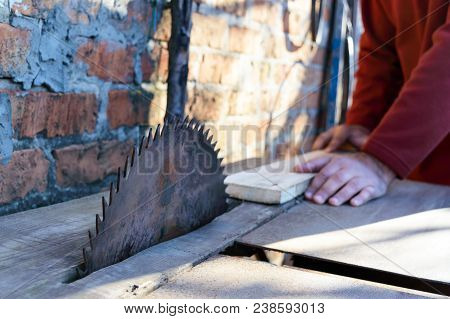 Sawmill. Old Machine For Sawing Boards. Circular Saws. Woodworking Industry. A Man Is Holding A Boar