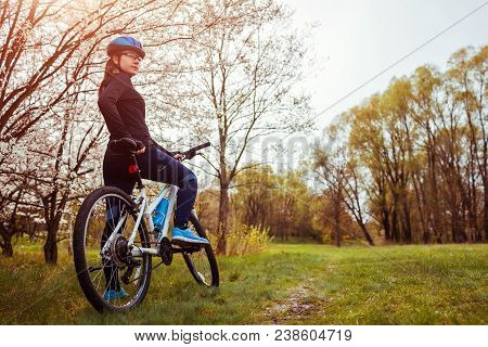Young Woman Riding A Bicycle In Spring Forest In The Morning. Helathy Lifestyle Concept. Active Way
