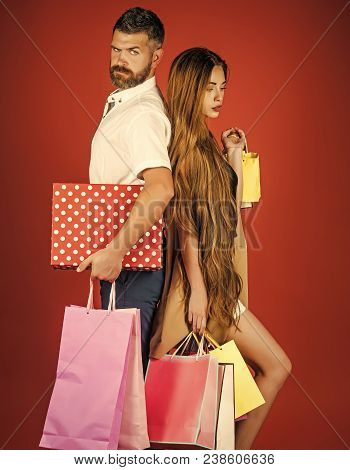 Couple In Love Hold Shopping Bag Near Red Wall. Black Friday, Happy Holiday, Relations. Girl And Bea