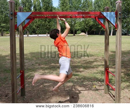 Boy With An Orange T-shirt Does Gymnastic Exercises Along A Path Equipped In A Park
