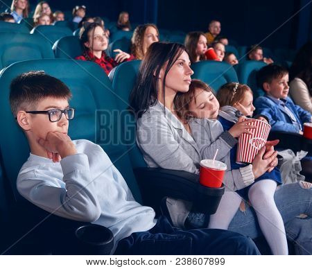 Spectators sitting in comfortable chairs and watching film in cinema. Boy looking with interest at screen with steadfast eyes. Little pretty girl with closed eyes sitting on her mom laps. poster