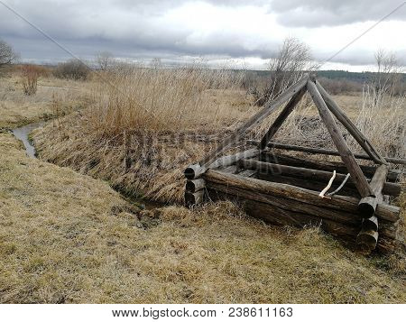An Old Wooden Well. A Wooden Well In The Field. A Wooden Well Against The Background Of Dry Grass.