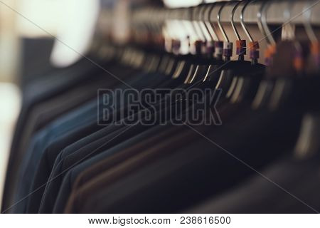 Close Up. Business Mens Suits Hang On Hangers In Boutique Of Business Clothes. Big Choice Of Suit. W