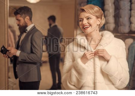 Luxury And Relationship Concept. Woman Tries Expensive Sable Overcoats. Man And Girl With Happy Face