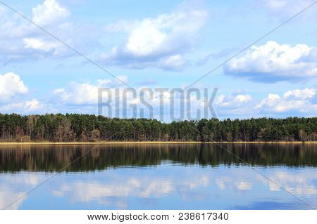 Lake in summer forest. Forest and nature lake. Forest and clouds reflected in the lake. Summer landscape. Russian nature. The green woods reflected in water. Fir and spruce forest in summer. Nature reserve. The lake in Russia. Travel in Russia