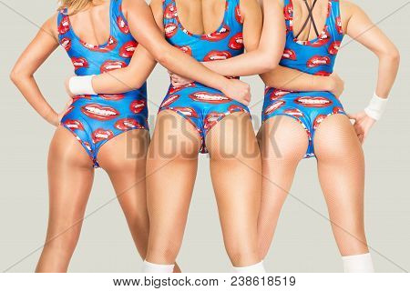Three Fitness Girls On Light Gray Background. Back View.