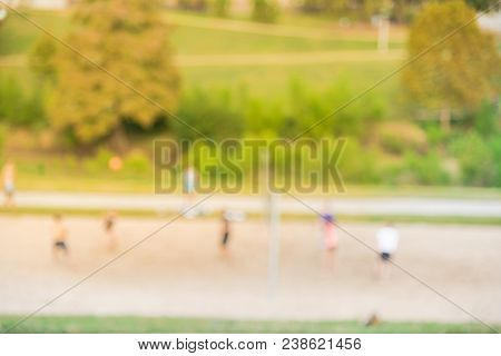 Blurred Image Group Of Caucasian Young People Playing Outdoor Volleyball In Summer At Urban Park In