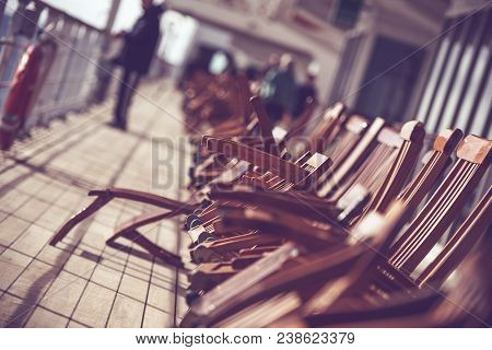 Cruise Ship Travels Photo Concept. Wooden Deck Chairs On The Vessel Main Deck.