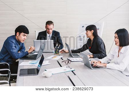 Businesspeople Using Laptops And Discussing Together In Meeting Room.teamwork Concept