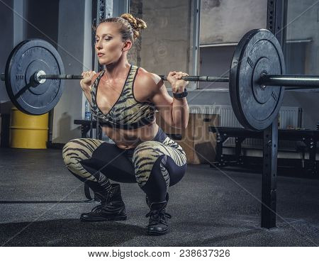 Athletic Blond Female Fitness Model Holding Heavy Barbell And Preparing For Squats.
