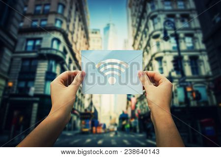 Woman Hands Holding A Paper Sheet With Wifi Symbol In The Middle Of The Street In A Big City. Dreami