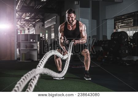 Muscular Powerful Aggressive Man Working Out With Rope In Functional Training Fitness Gym
