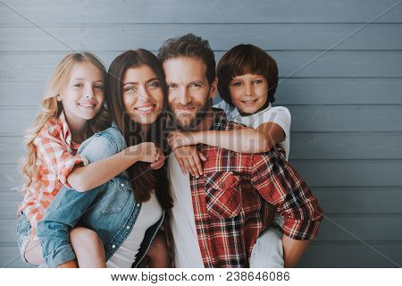 Portrait Of Happy Parents With Lovely Children. Full Healthy Families Concept. Joyful Parents Spend