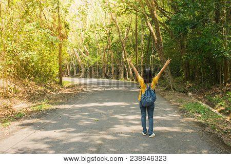 Alone Woman Traveler Or Backpacker Walking Along Countryside Road Among Green Trees, She Raise Hands