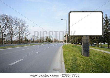 Blank Billboard In The Side Of A Road , Fork Or Crossroad With Blank Billboard.