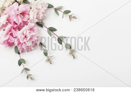 Bunch Of Beautiful Flowers And Eucalyptus Leaves On White Table Top View. Flat Lay Style.