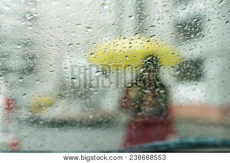 Wet Rain Drops On Glass. Woman With Yellow Silhouette Through Wet Glass