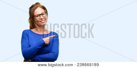 Middle age woman wearing wool sweater and glasses pointing away side with finger isolated blue background
