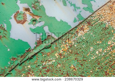 painted iron surface with a large rusty and metal corrosion, chipped paint, old background with peeling and cracking paint, texture poster