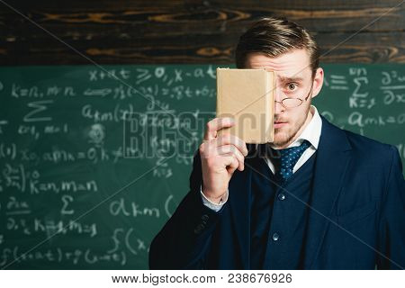Surprised Guy Hiding His Face Behind Book Cover. Portrait Of Young Scholar Isolated On Blurred Green