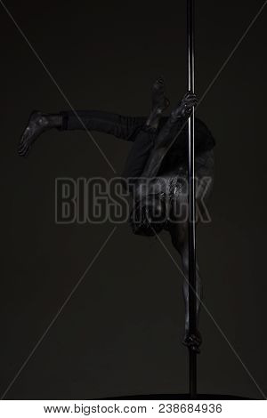 Young Strong Pole Dance Man On Dark Background. Guy With Nude Torso Performing Pole Dancing Moves On
