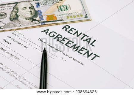 Pen And Us Dollar Banknotes Money On Rental Agreement Form Document, Ready To Sign Contract, Propert