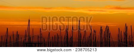 silhouettes of yacht masts, orange sunrise in a port
