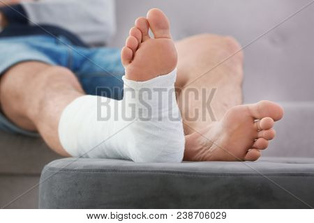 Young Man With Broken Leg In Cast Sitting On Sofa At Home