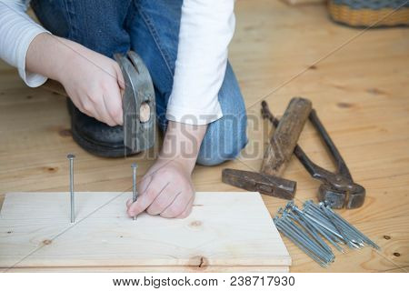 Child In A Long-sleeved T-shirt And Jeans Sits On A Wooden Floor And Clogs The Nails Into The Wood W