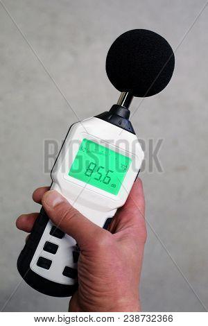 Hand Holding Sound Level Meter. Vertical Image.