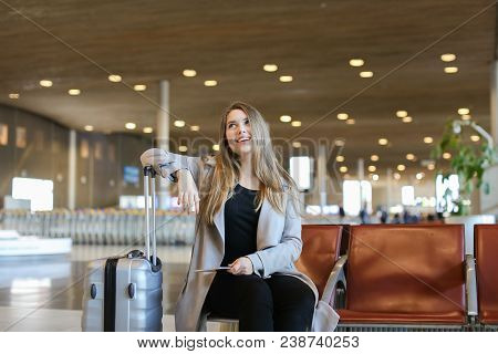 Gladden Beautiful Woman Making Video Call By Modern Tablet In Airport Waiting Room And Sitting Near