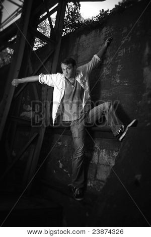 Black And White Photo Of A Man Climbing A Wall