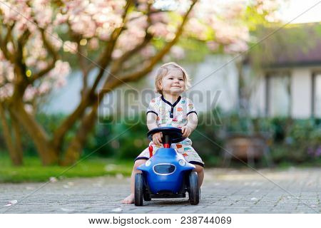 Cute Little Baby Girl Playing With Blue Small Toy Car In Garden Of Home Or Nursery. Adorable Beautif