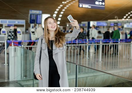 Young Woman Making Selfie By Smartphone Front Camera At Airport. Concept Of Social Networks And Trav