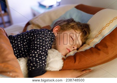 Little Preschool Kid Boy Sleeping In Bed With Colorful Lamp. School Child Dreaming And Holding Plush