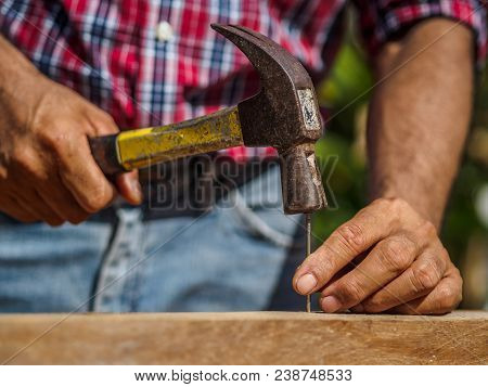 Close Up Of Hammering A Nail Into Wooden Board. Profession, Carpentry, Woodwork And People Concept.