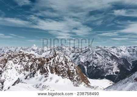 Alpine Panoramic Alpine Landscape. Mountain Peaks In The Snow On A Background Cloudy Sky