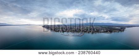 Panoramic view of a turqoise lake Geneva at sunset overlooking a small town with a habor taken from a drone